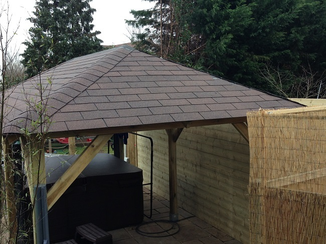 Large open sided gazebo in a garden in Weybridge, Surrey. The structure is covered with brown felt roof shingles for awtertight finish.