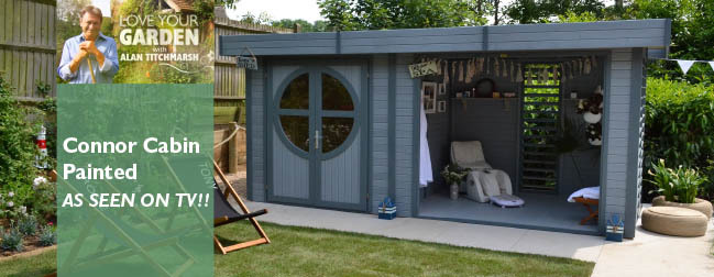 Connor log cabin with a modern painted finish within a residential garden setting