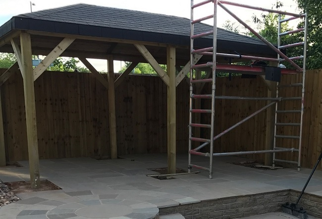 Grande wooden garden gazebo with a black shingle roof built within a patio area of a property in Warwickshire