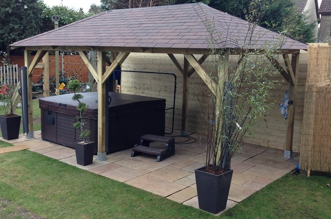 Superior open sided pitched roof wooden gazebo used as a canopy for a hot tub